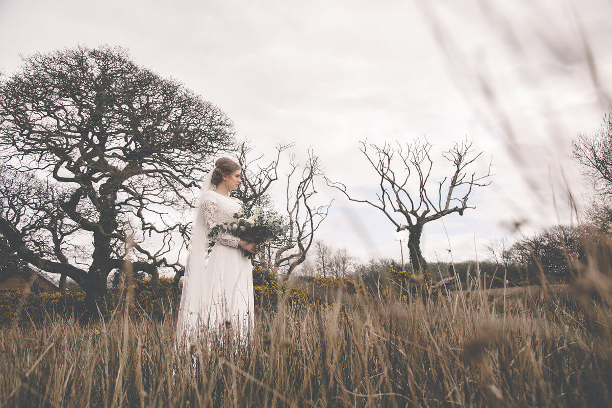 A picture of a bride standing in a field during a winter wedding ceremony.