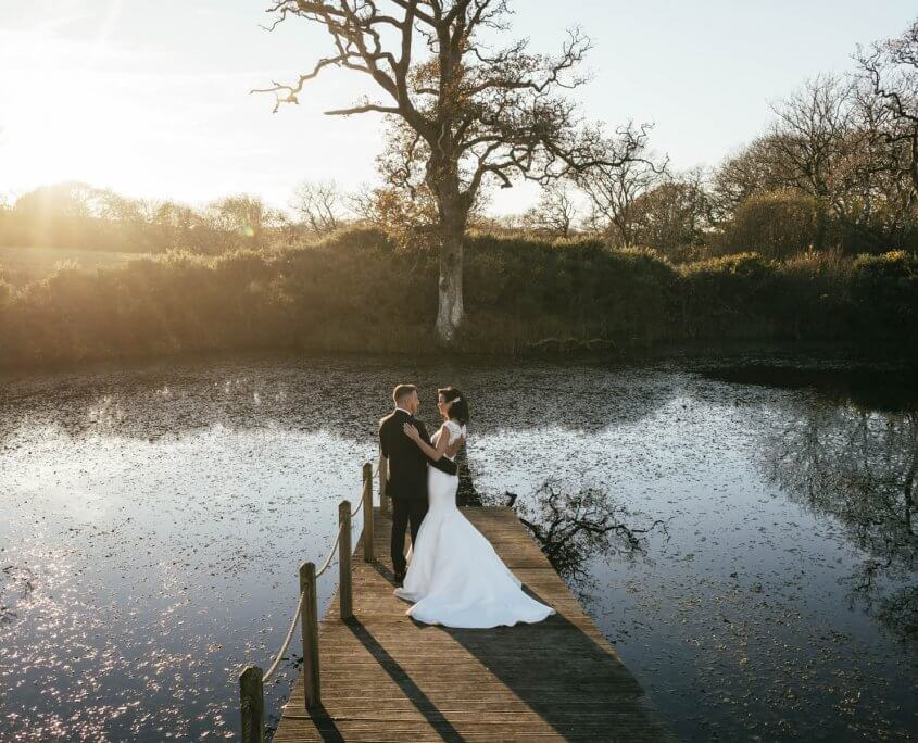 A picture of the happy couple posing next to a lake during a winter wedding ceremony.