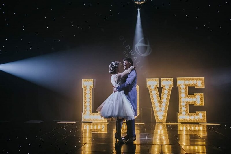 An image of a couple dancing in front of an illuminated love sign