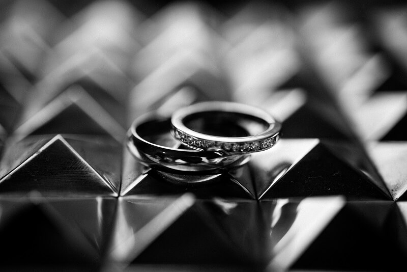 A black and white image of wedding rings.