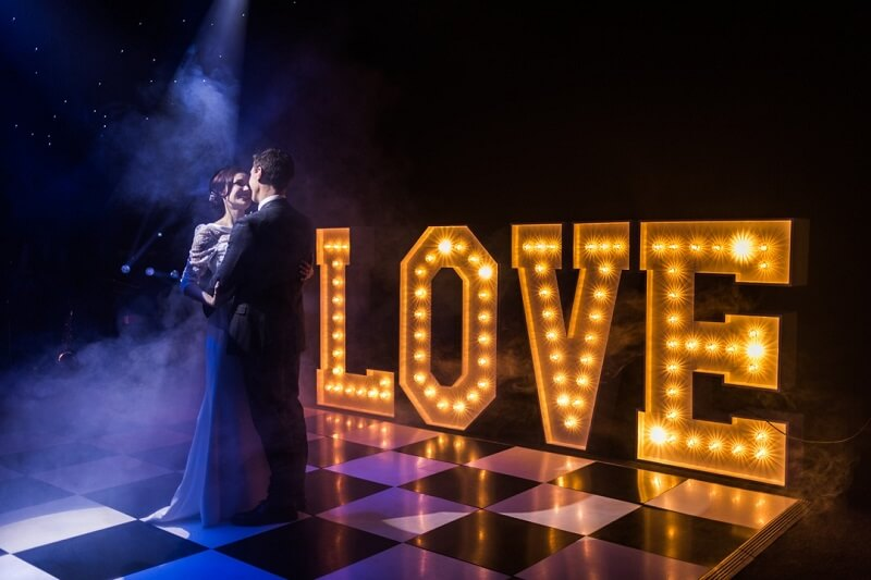 Image of a couple on the dance floor at a wedding reception, with an illuminated love sign in the background.