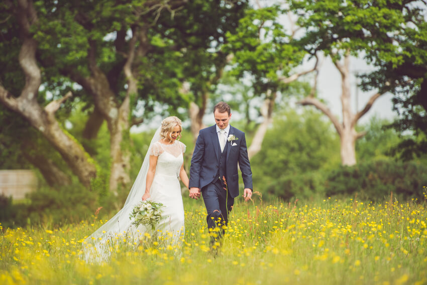 An image of a married couple strolling through the grounds at Oldwalls Gower.