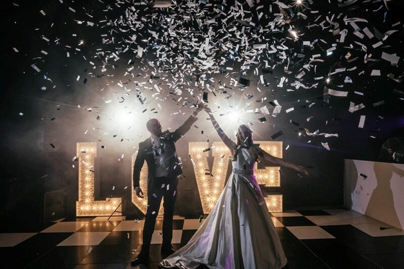 Bride and groom stand with arms in the air in front of a giant love sign as confetti falls
