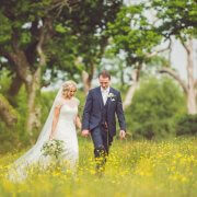 Bride and groom walking hand in hand through a field of flowers