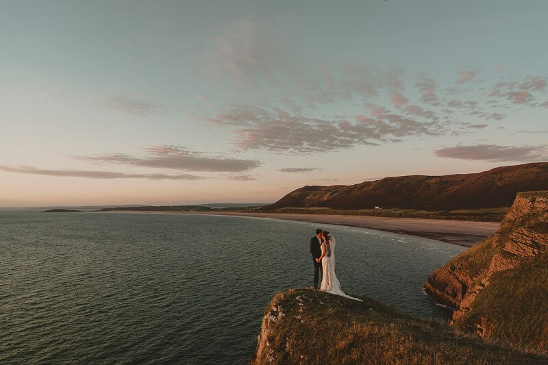 Bride and groom standing on cliff overlooking the Gower peninsula