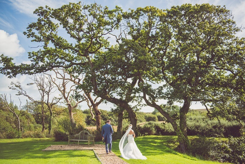 Bride and groom walking through the grounds of Oldwalls Gower