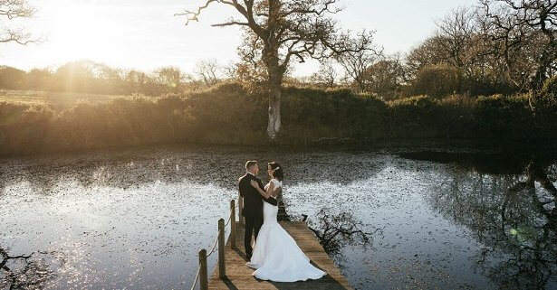 Bride and groom by lake in autumn