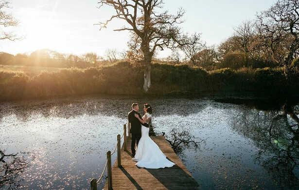 Bride and groom standing on the jetty at Oldwalls lake