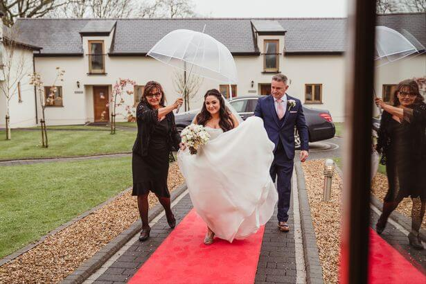 Bride arriving in the rain at Oldwalls