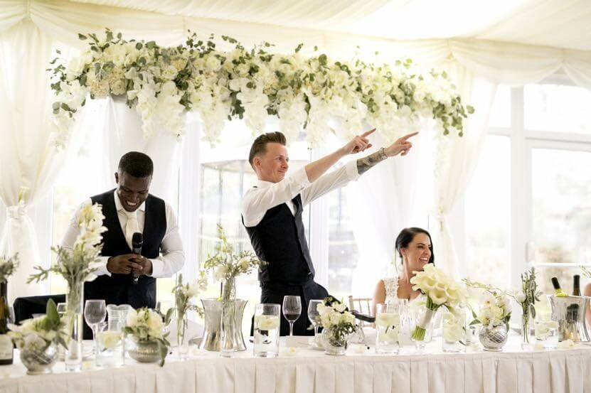 Groom celebrating at a table next to his best man and bride at their wedding venue surrounded by flowers.