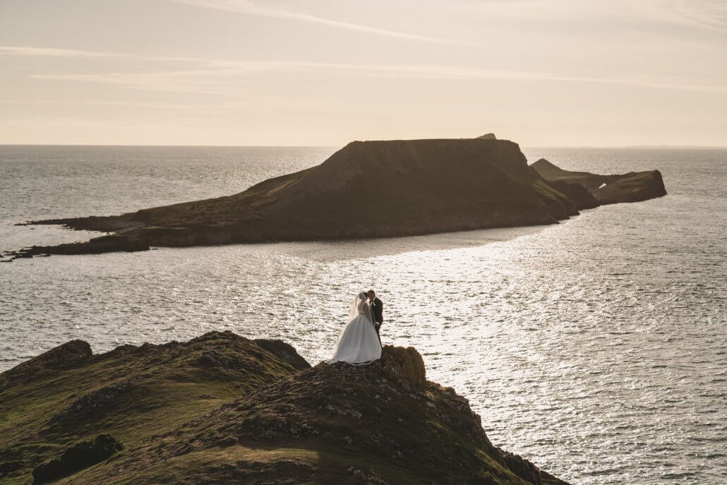 Bride and Groom overlooking the beautiful Gower in Swansea whilst the sunsets on a summer day.