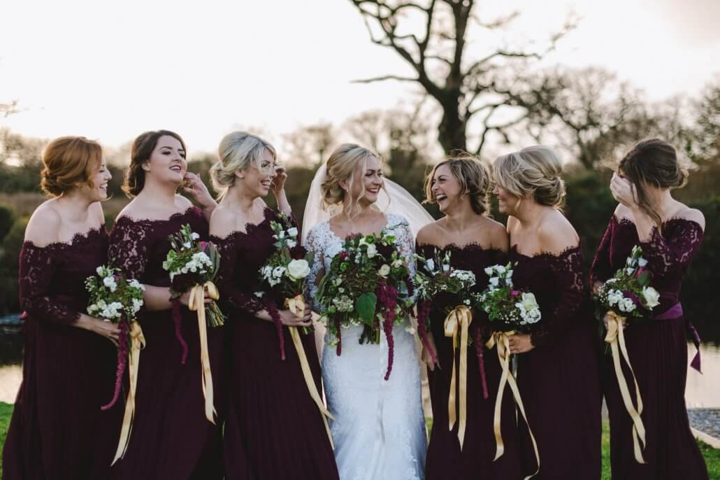 Bride in white dress surrounded by her bridesmaids in a deep purple style dress all holding a bouquet of flowers.