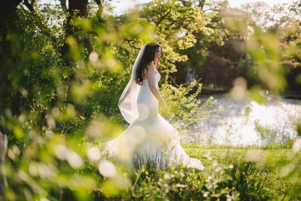 bride on her wedding day wearing a sleek white wedding dress in south wales, gower on a summers day.