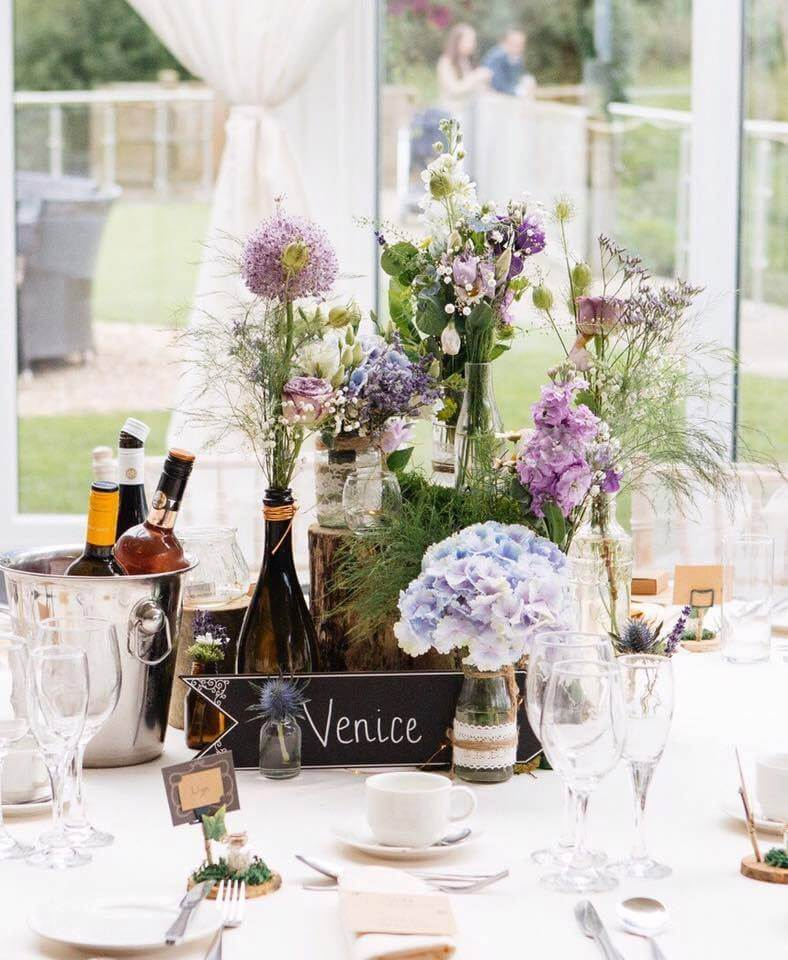 Flower table display at a summer wedding venue with bottles of alchohol on the table at Oldwalls wedding venue.