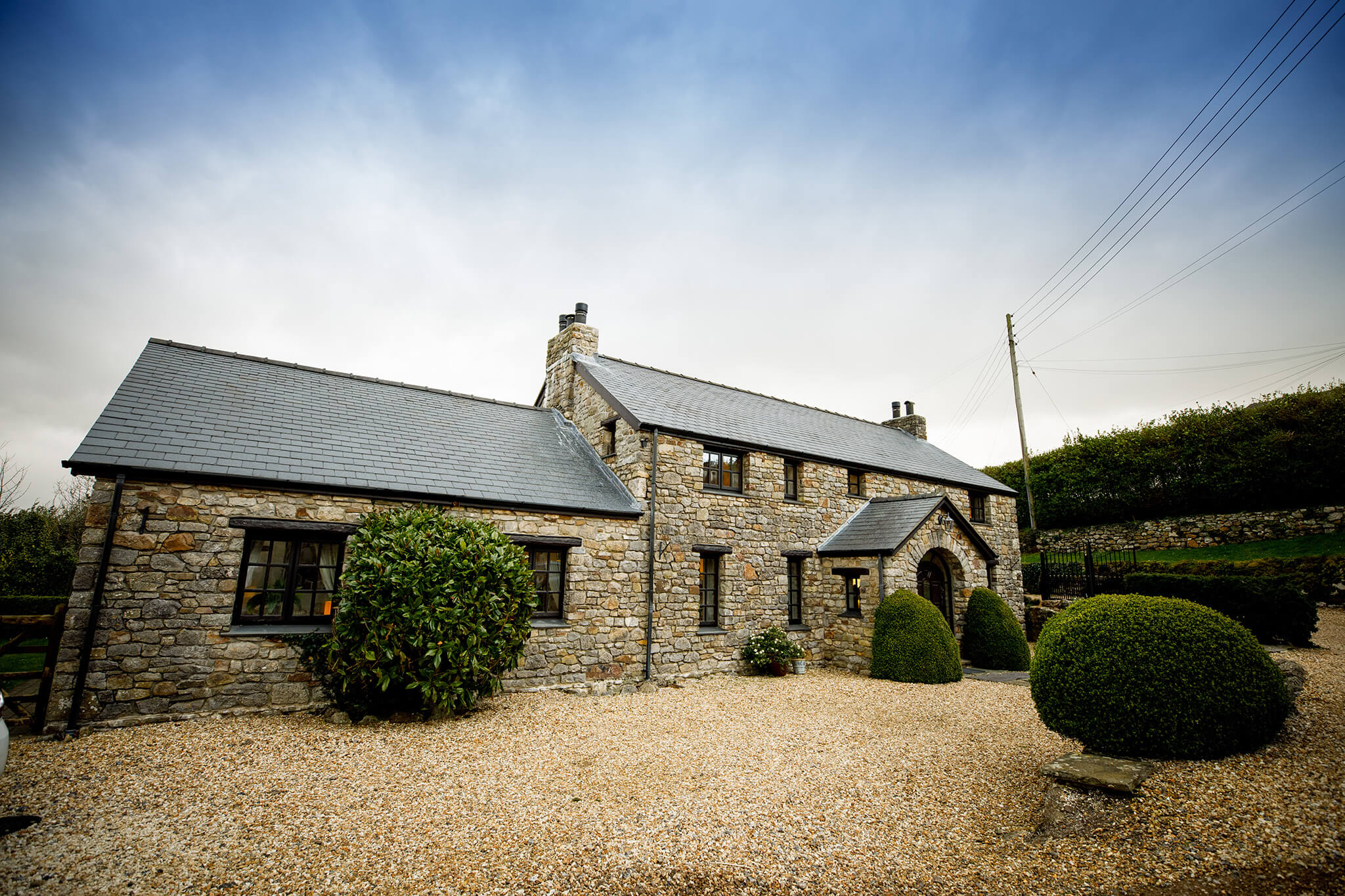 rustic wedding accomodation. Stone walled home with a pebble drive and decorative bushes at the south wales wedding venue, fairyhill