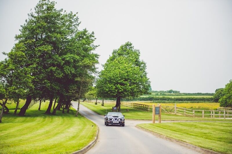 vintage wedding car bringing the bride and groom up the drive way at Oldwalls' famous scenic south wales wedding venue