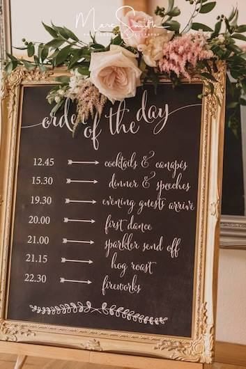 wedding planner organisation checklist decorated with a bouquet of flowers on a chalkboard