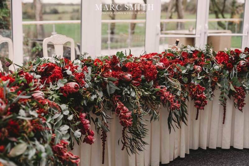 beautiful floral decorations at oldwalls fairyhill venue. Red flowers in amongst green leave wreathes.