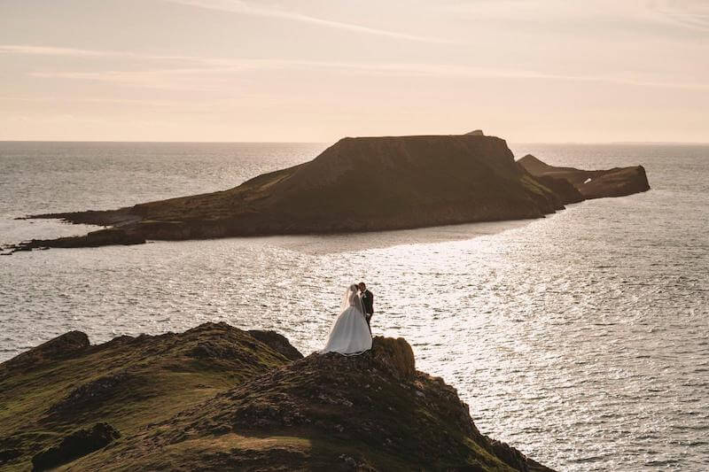 dramatic photo of a bride and groom in south wales overlooking the sea with an island in the backdrop a the sun begins to set on their big day