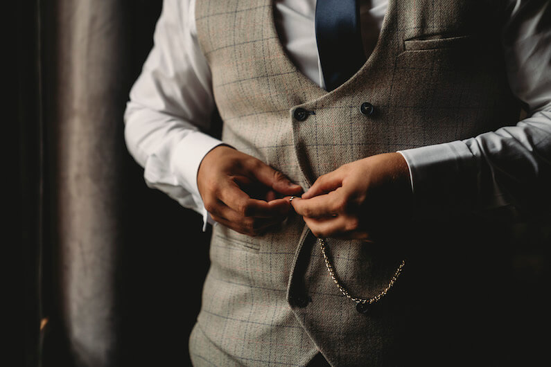 smartly dressed three piece suited man buttoning up his vest with a pocket watch connected ready for a fantastic wedding