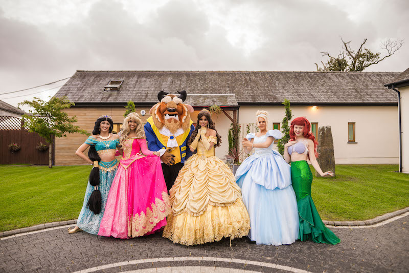 Guests dressed as Disney princesses along side the Beast from Disney