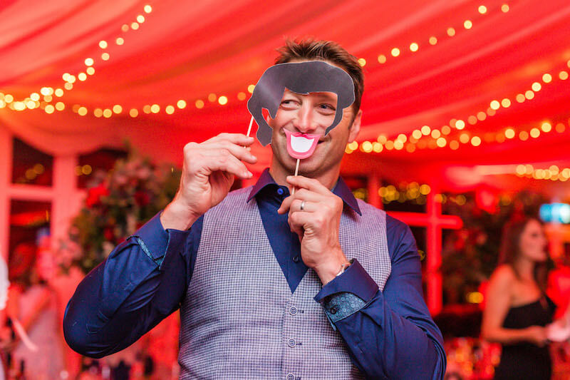 wedding guest posing with fun party supplies at a wedding venue