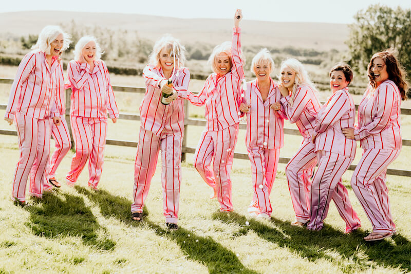 blonde bridesmaids at a wedding in south wales popping a bottle of champagne in pink striped pyjamas in a field