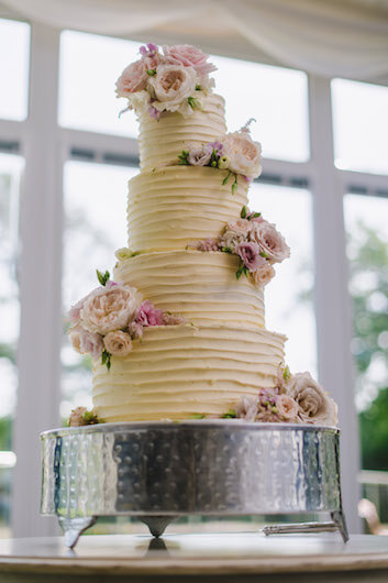 four tier wedding cake in yellow with decorative pink flowers